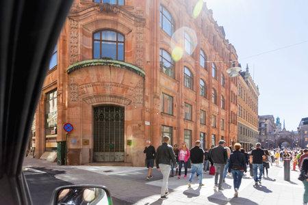 STOCKHOLM, SWEDEN - July 06, 2017. Tourists walk pass Sydsvenska kredaktiebolaget, old building built in 1909 by Gustaf Wickman. Architectural landmark in art nouveau style built in red Scanian sandstone.