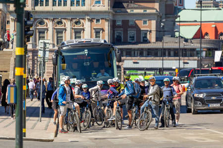 STOCKHOLM, SWEDEN - July 06, 2017. Group of people on bicycles, cars and bus are waiting for green traffic lights. Traffic on central street of capital of Sweden.