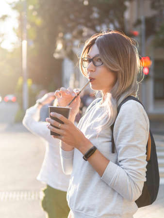 Woman with curly hair and eyeglasses drinks cappuccino with straw. Pretty female waits for green traffic light on pedestrian crossing. Woman with cup of take away coffee. Street life in town.
