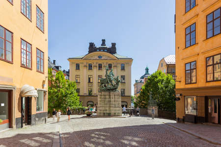 STOCKHOLM, SWEDEN - July 06, 2017. Tourists walk around bronze replica of Saint George and the Dragon sculpture by Bernt Notke. Antique buildings on Kopmantorget or Merchant's Square.