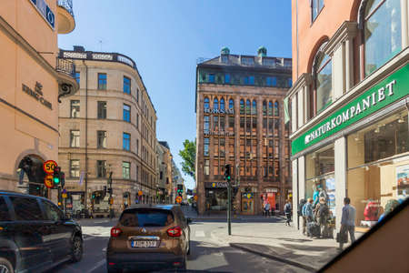 STOCKHOLM, SWEDEN - July 06, 2017. Traffic on Norrlandsgatan street. Cars wait for green traffic light, local people and tourists walk on pavement pass large windows of hotels and stores. Redactioneel