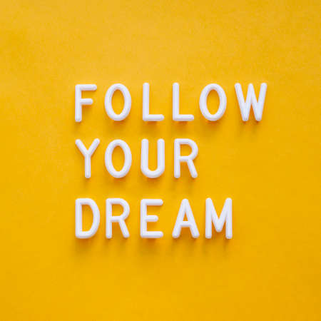 Follow your dream. Motivating and inspiring phrase on bright yellow background. Top view on lifting spirit message. Creative rise. Reklamní fotografie