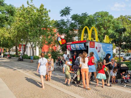 KEMER, TURKEY - May 13, 2018. Crowd of people near small McDonald's kiosk with ice-cream. Mothers with children in strollers wait in turn to buy cold dessert.