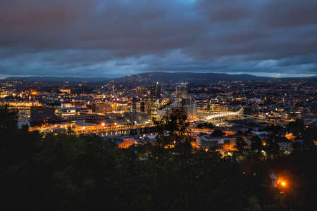 Night panoramic view of Oslo, capital of Norway. Dark cloudscape ower capital of Norway. Scandinavian city with lighted buildings and bridges, surrounded by forests.