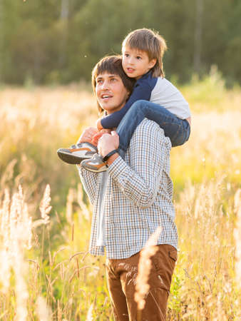 Father carries his son on shoulders. Family time outdoors. Man with child on autumn field at sunset. Dad and son explores nature together. Stockfoto