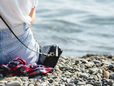 Woman in blue jeans with purse sits on pebble beach. Rear view of woman enjoying sunlight at seaside. Long awaited vacations on ocean coast. Stockfoto
