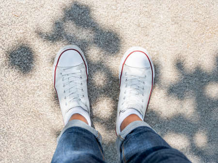 Woman feet in white sneakers on stone pavement. Top view on casual clothing and shoes at sunlight. Summer vibes. Modern urban fashion. Stockfoto