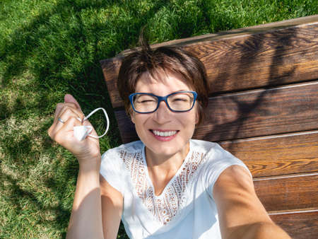 Smiling woman takes off medical protective mask to make selfie on her smartphone. Female in eyeglasses has a rest in urban park Stockfoto