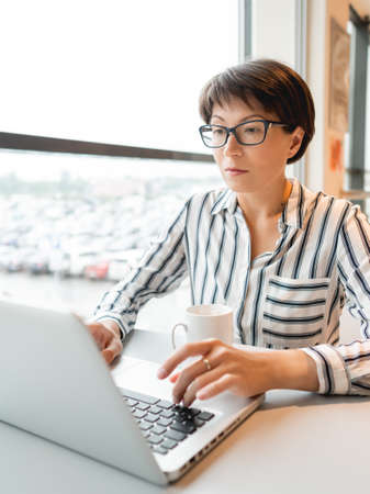 Business woman works with laptop in co-working center. Workplace for freelancers in business center.