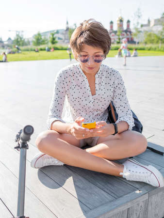 Woman in colorful sunglasses sits on wooden open stage in public park. Pretty female in casual clothes texting on smartphone after riding kick scooter, eco-friendly urban transport.