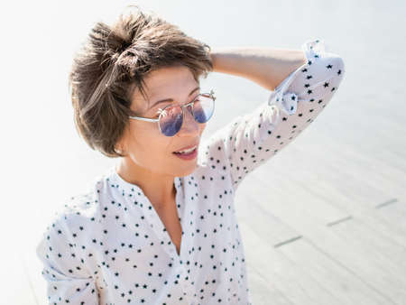 Wind ruffles short hair of freckled woman in colorful sunglasses. Smiling woman at open wooden scene of urban park. Summer vibes. Sincere emotions.