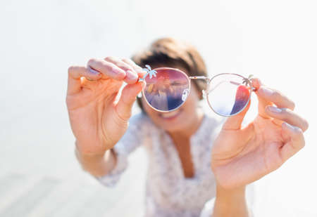 Woman with short hair looks through colorful sunglasses. Smiling woman at open wooden scene of urban park. Summer vibes. Sincere emotions. Stockfoto