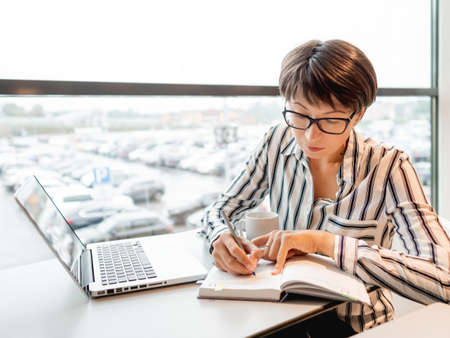 Business woman works with laptop and paper organizer in co-working center. Workplace for freelancers in business center.