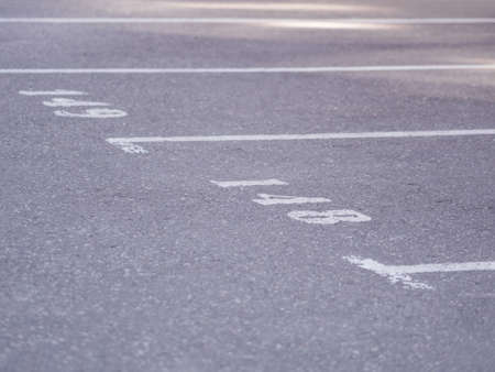City parking lot. White numbers drawn on asphalt roadbed. Outdoor Parking spaces are reserved for cars. Stockfoto