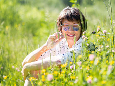 Woman in colorful sunglasses, enjoys sunlight and flower fragrance on grass field. Summer vibes. Relax outdoors. Self-soothing.