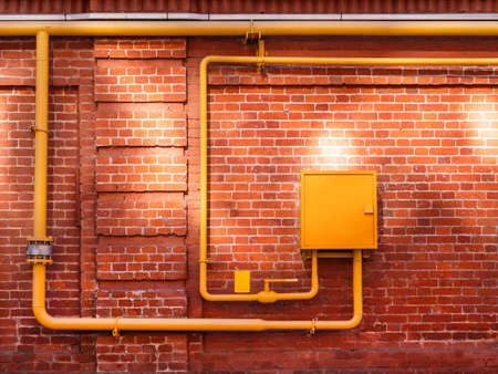 Red brick wall with yellow gas pipes and sunbeams. Old wall with sun reflections. Old building with shabby surface.
