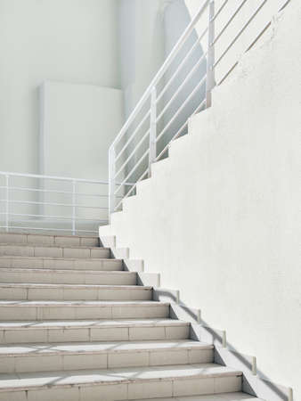 White exterior of outdoor staircase with railing. Sunlight and shadow on stone steps. Urban geometry.