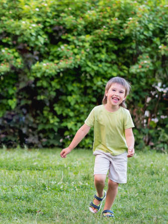 Laughing kid runs on grass lawn at backyard. Happy childhood. Summer vacation. Cheerful child plays outdoors. Active recreation. Leisure activity in warm season. Stockfoto