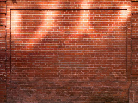 Red brick wall with sunbeams. Old wall with sun reflections at upper part. Old building with shabby surface. Mock up. Stockfoto