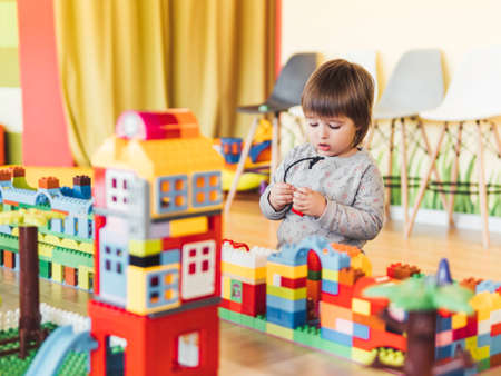 Toddler boy is playing in kidsroom with colorful constructor. Educational toy block in his hands. Kid is busy with toy bricks. Stockfoto