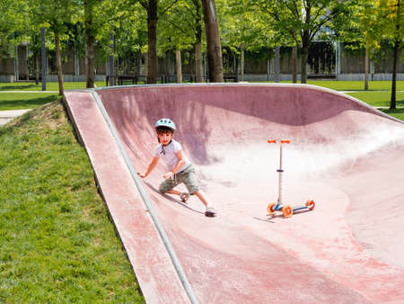 Little boy fell off kick scooter while riding in skate park. Special concrete bowl structures in urban park. Training to skate at summer.
