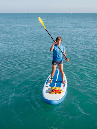 Paddle boarder. Sportsman paddling on stand up paddleboard. SUP surfing. Active lifestyle. Outdoor recreation. Vacation on seaside. Stockfoto