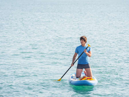 Handsome paddle boarder. Sportsman on knees paddling on stand up paddleboard. SUP surfing. Active lifestyle. Outdoor recreation. Vacation on seaside. Stockfoto