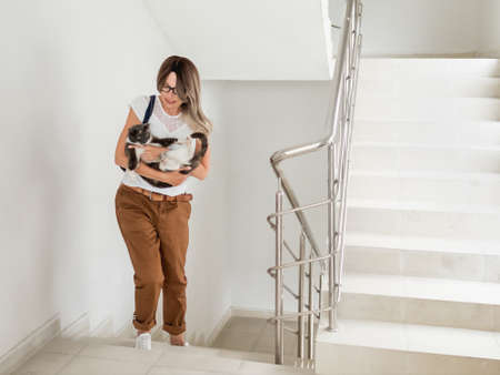 Woman carries home fluffy stray cat. Woman and pet on indoor staircase of apartment building. Undomestic animal purrs of pleasure. Pet adoption. Taking care of homeless animals.