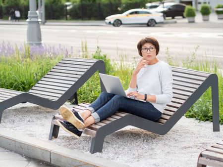 Woman sits with laptop on urban park bench. Freelancer at work. Student learns remotely from outdoors. Modern lifestyle. Stockfoto