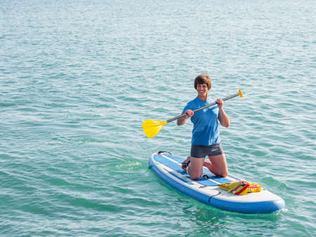 Paddle boarder. Sportsman on knees paddling on stand up paddleboard. SUP surfing. Active lifestyle. Outdoor recreation. Vacation on seaside. Stockfoto