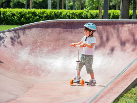 Little boy rides kick scooter in skate park. Special concrete bowl structures in urban park. Training to skate at summer.