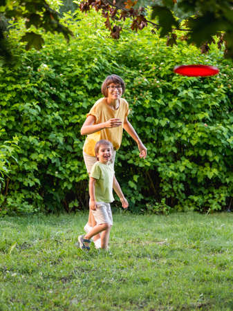 Mother and son play flying disk on grass lawn. Summer vibes. Outdoor leisure activity. Family life. Sports game at backyard.