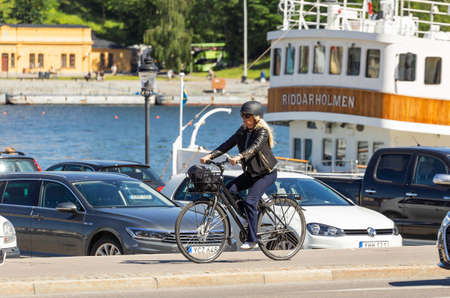 STOCKHOLM, SWEDEN - July 06, 2017. Woman in helmet rides bicycle along the sea embankment. Outdoor recreation. Cycling trip to Europe.