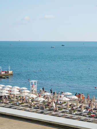 SOCHI, RUSSIA - May 27, 2021. People relaxing on beach in sun loungers under beach umbrellas. Vacation on seaside. Sunny day on Black sea coast. Stockfoto