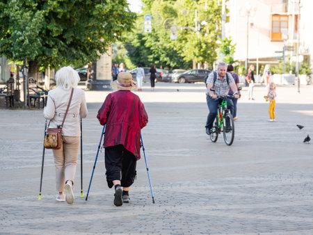 KRASNODAR, RUSSIA - July 02, 2021. Two old Nordic walking ladies and old man riding bicycle on street. Healthy leisure activity for elder people. Redactioneel