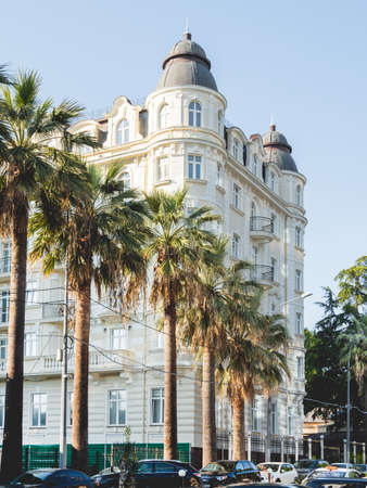 SOCHI, RUSSIA - May 27, 2021. Facade of apartment hotel Matisse. Beautiful building with palm trees alley at sunny day.