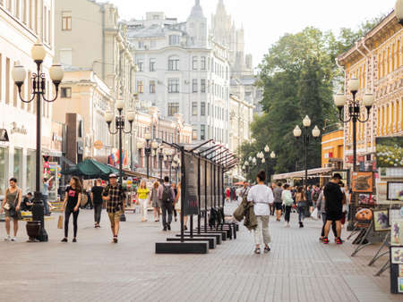 MOSCOW, RUSSIA - August 08, 2021. Local people and tourists walk down famous Arbat street with souvenir shops and boutiques.