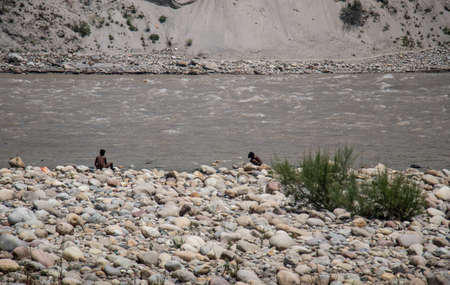 Wide portrait of two young brown Indian boys sitting on a riverside under the bright sunlight in India, relaxing and searching for some stuff among the stoney banks of the river Ganges in Srinagar, India, 5K