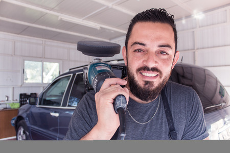 cleaning service: Man holds car polishing tool in the hands and smile