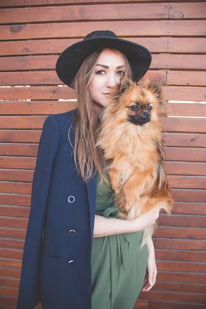 Jong mooi meisje in een zwarte hoed en een lange kleding op een bruine houten achtergrond met kleine hond Stockfoto