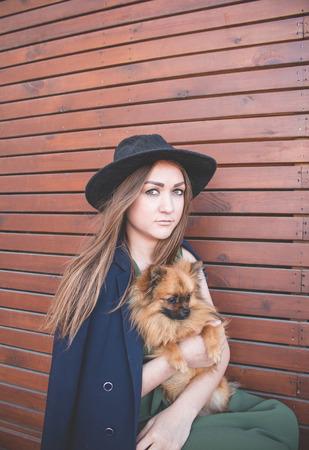 Jong mooi meisje in een zwarte hoed en een lange kleding op een bruine houten achtergrond met kleine hond Stockfoto - 75376472