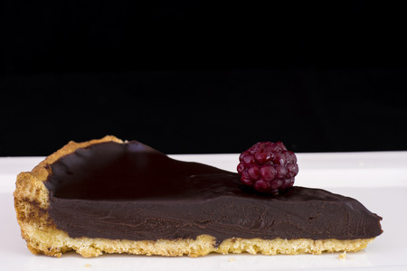 Slice of delicious chocolate tart with raspberry served on white plate.