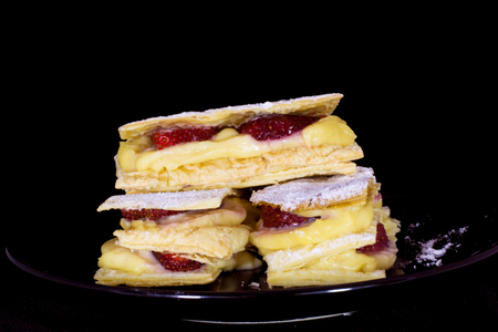 Delicious fresh baked puff pastry with fresh strawberries isolated on black background Imagens