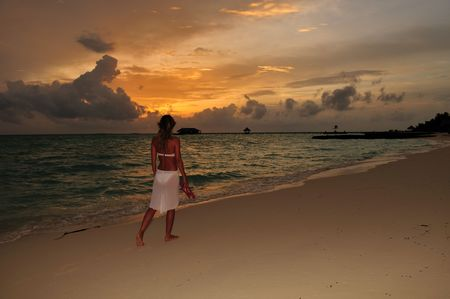 woman wearing a flowing white sarong on a tropical beach  photo