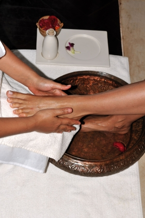 Woman enjoying a feet massage in a spa setting (close up on feet) photo