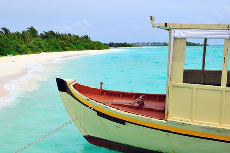 Old traditional boat anchored on a sandy beach in Maldives photo