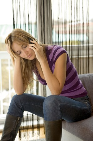 woman talking on her cell phone with a sad expression Stock Photo