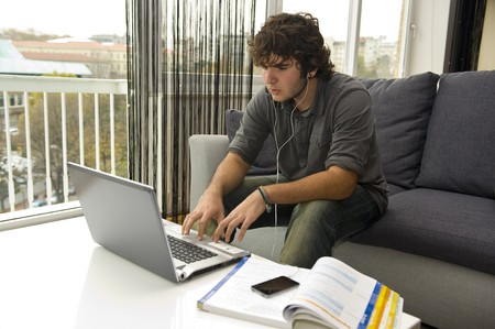 teenager studying and listening to music Stock Photo