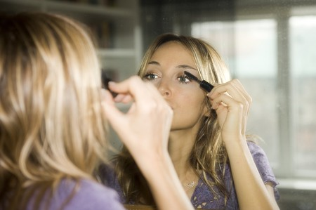 woman applying makeup to her face photo