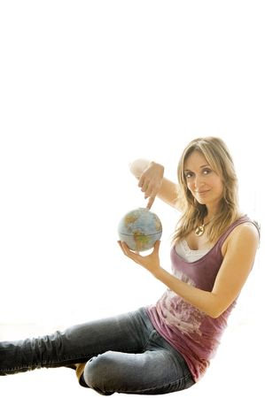Young woman holding a small globe in her hand. photo